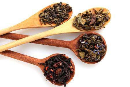 hojas secas: Diversas clases de t� seco verde y negro en cuchara woooden aislado en blanco