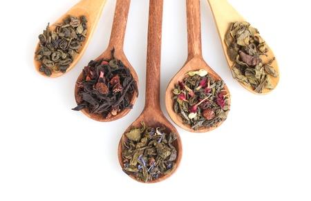 loose leaf: Los diferentes tipos de t� seco verde y negro en una cuchara woooden aislado en blanco