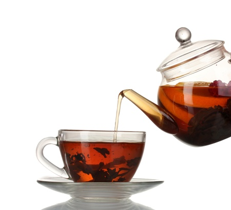 mate: Glass teapot pouring black tea into cup isolated on white Stock Photo