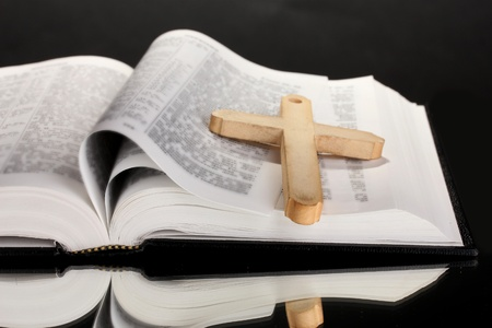 bible open: Russian bible and wooden cross on black background Stock Photo