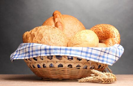 delicious bread in basket and ears on wooden table on gray background Stock Photo - 13104244