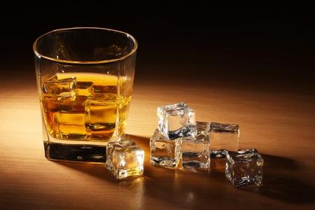 scotch: glas Schotse whisky en ijs op de houten tafel