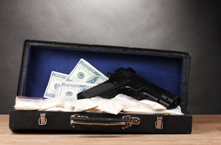 drug deals: Cocaine, dollars and handgun in case on wooden table on grey background Stock Photo