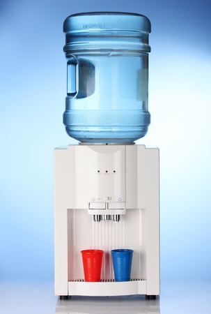 hot water tap: Electric water cooler on blue background Stock Photo