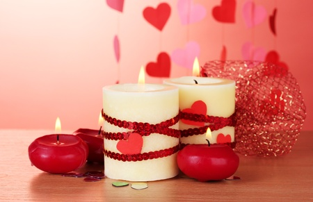 candles for Valentine's Day on wooden table on red background Stock Photo - 13104311