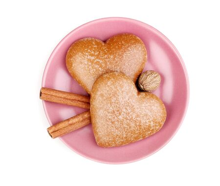 Heart-shaped cookies with cinnamon and nutmeg on saucer isolated on white photo
