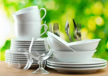 Sauberes Geschirr auf Holztisch auf grünem Hintergrund
