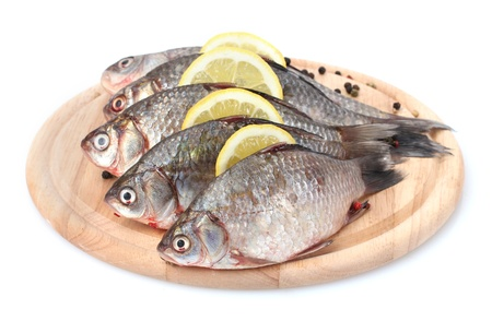 Fresh fishes with lemon and spice on wooden cutting board isolated on white photo