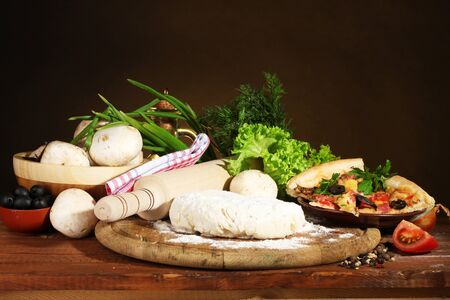 delicious pizza dough, spices and vegetables on wooden table on brown background photo
