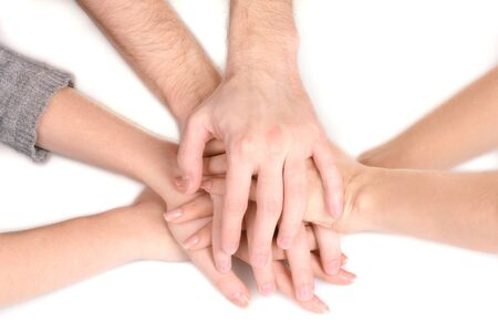 joined hands: group of young peoples hands isolated on white