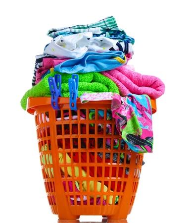 Clothes in orange plastic basket isolated on white Stock Photo - 13178399