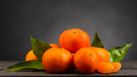 tangerines with leaves on wooden table on grey background photo
