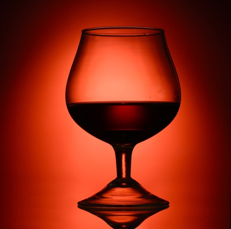 Glass of cognac on red background Stock Photo - 13178646
