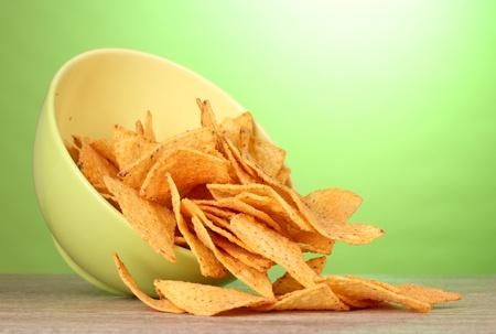 overturn: patatine gustose in una ciotola verde sulla tavola di legno su sfondo verde Archivio Fotografico