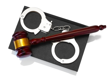 wooden gavel, handcuffs and book isolated on white photo