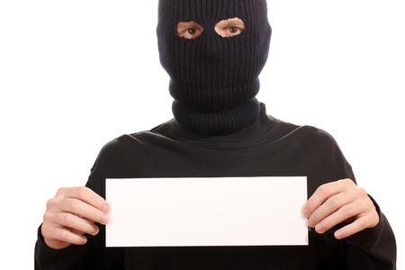 hijacker: Bandido en la m�scara de negro con la tarjeta en blanco aislado en blanco Foto de archivo