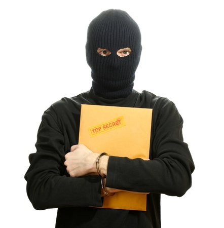 Bandit in black mask in handcuffs with top secret envelope isolated on white Stock Photo - 13177925