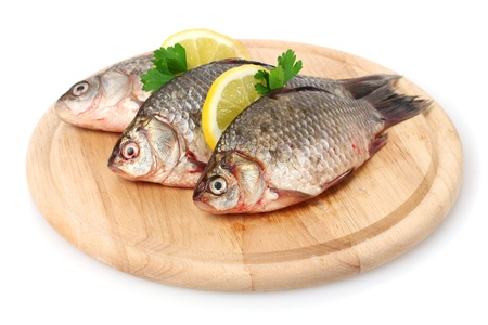 Fresh fishes with lemon and parsley on wooden cutting board isolated on white photo
