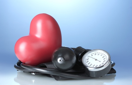 hypertensive: Black tonometer and heart on blue background Stock Photo