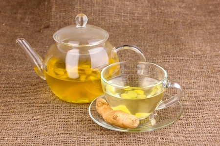 Healthy ginger tea in kettle and cup on sackcloth photo