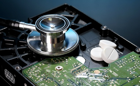 corrupt practice: Stethoscope on hard disk drive on dark blue background