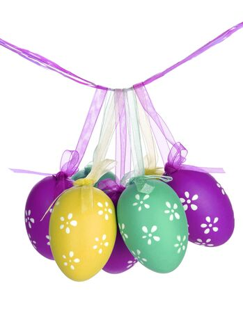 Colorful easter eggs hanging on ribbons isolated on white photo