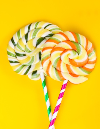 Colorful lollipops on yellow background photo