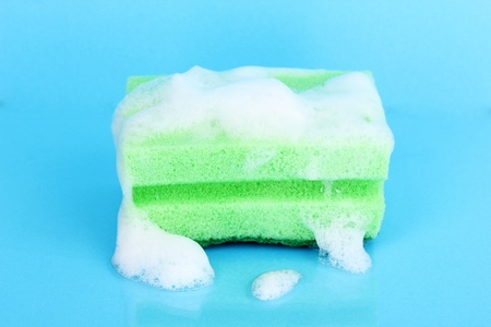 dishwashing: Sponge with foam of dishwashing liquid on blue background