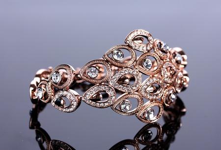 jewellery design: Beautiful golden bracelet with precious stones on grey background