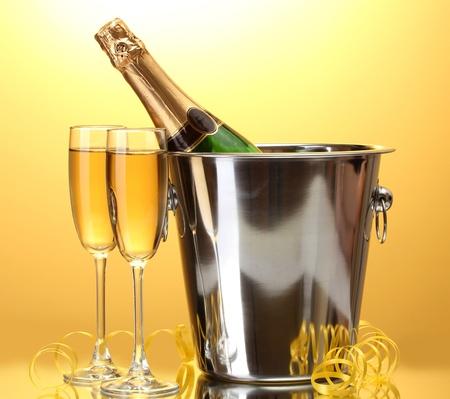botella champagne: Botella de Champagne en un cubo con hielo y copas de champ�n, sobre fondo amarillo