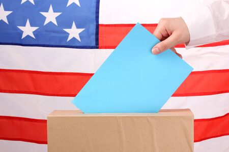 voting ballot: Hand with voting ballot and box on Flag of USA