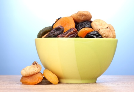 Dried fruits in green bowl on wooden table on blue background photo