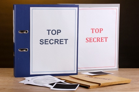 Envelopes and folders with top secret stamp and photo papers with CD disks on wooden table on brown background Stock Photo - 13223863