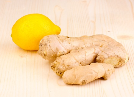 Ginger with lemon on wooden background photo