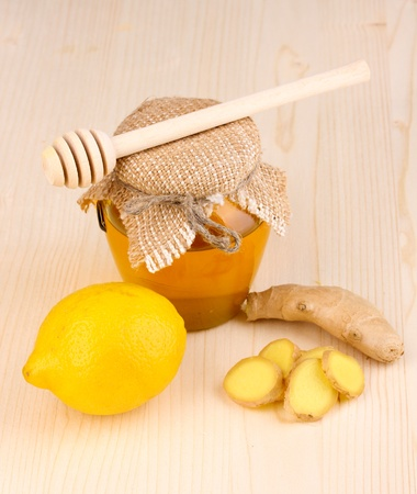 Ginger with lemon and honey on wooden background photo