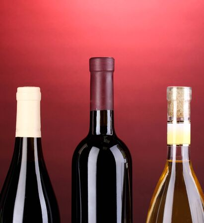 Bottles of great wine on red background photo