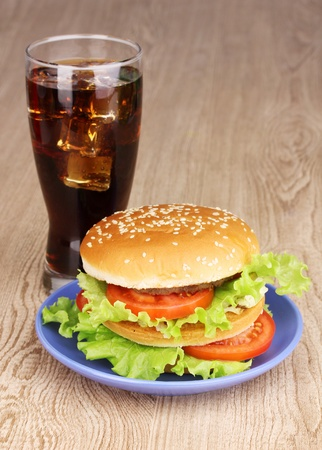Big and tasty hamburger on plate with cola on wooden table photo