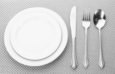 White empty plates with fork, spoon and knife on a grey tablecloth photo