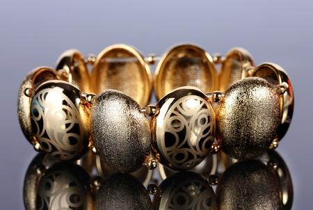 Beautiful golden bracelet on grey background photo