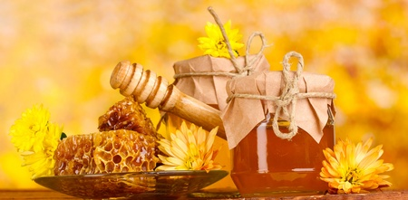 drizzler: two jars of honey,honeycombs and wooden drizzler on table on yellow background