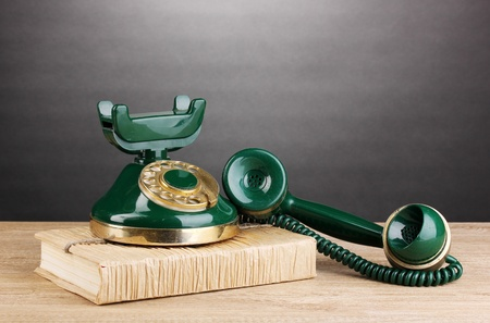 dialplate: Retro phone standing on book on wooden table on grey background