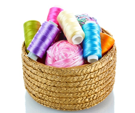 basket embroidery: bright bobbin thread in basket isolated on white  Stock Photo
