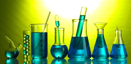 Test-tubes with blue liquid on green background photo