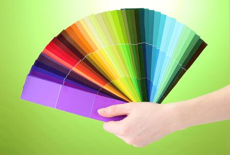 hand holding bright palette of colors on green background Stock Photo - 13265659