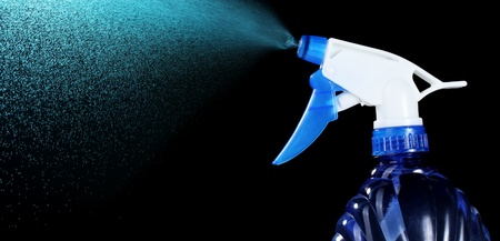 woman squirt: hand holding spray bottle and spraying on black background Stock Photo