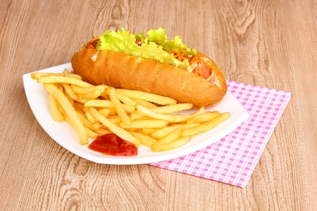 Appetizing hot dog with fried potatoes on plate on wooden table photo