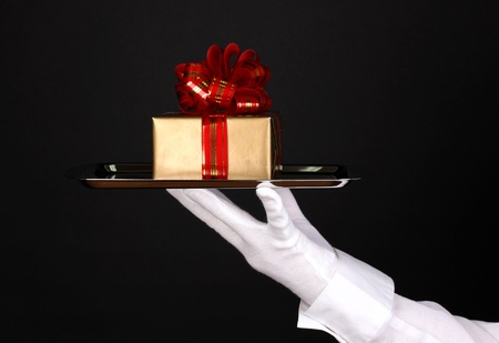 Hand in glove holding silver tray with giftbox isolated on black Stock Photo - 13267308
