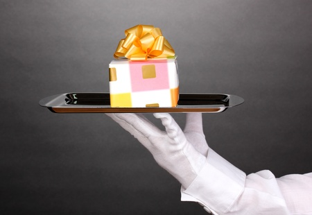 Hand in glove holding silver tray with giftbox on grey background Stock Photo - 13267282