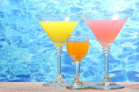 exotic cocktails on table on blue sea background photo