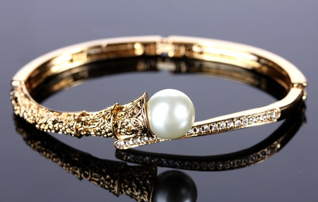 Beautiful golden bracelet with pearl on grey background photo